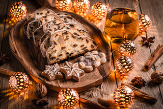 Christmas Stollen and cookies with apple mulled wine and Christmas lights. Traditional Sweet Fruit Loaf with icing sugar.