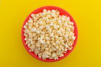 High angle view of popcorn in red bowl on yellow background