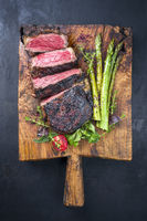 Barbecue dry aged wagyu entrecote beef steak with lettuce and green asparagus as top view on an old rustic wooden cutting board with copy space
