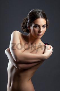 Portrait of hot brunette posing topless in studio
