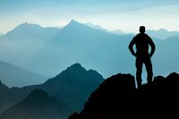 One Man reaching summit after climbing and hiking enjoying freedom and looking towards mountains silhouettes panorama during sunrise.