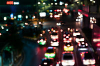 Defocussed urban traffic background at night with colourful bokeh - Blurred city congestion at road junction backdrop with glare from nearby shops and cars with copy space -Metropolis downtown concept