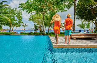 Young couple by poolside. Resort swimming pool at Seychelles.