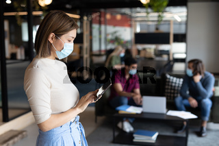 Asian businesswoman wearing face mask using tablet in creative office