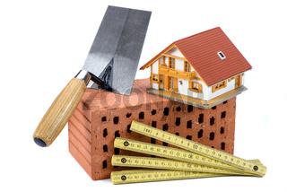 Ziegelsteine und Werkzeug als Symbol für Hausbau