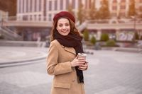 Parisian young woman holding reusable mug with coffee standing outdoors. Portrait of stylish young woman wearing autumn coat and red beret outdoors. Autumn accessories