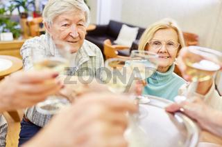 Senioren Paar feiert mit einem Glas Weißwein Geburtstag oder Hochzeitstag