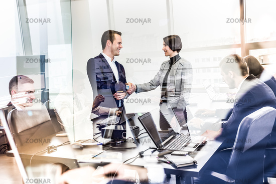Confident business people shaking hands in moder corporate office.