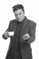Studio shot of angry Caucasian businessman holding coffee cup and pointing finger