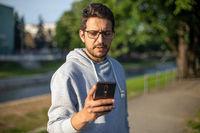 Man on smartphone in park, back light