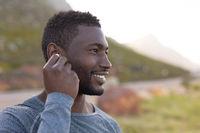 Portrait of fit african american man in sportswear putting earphones in in tall grass