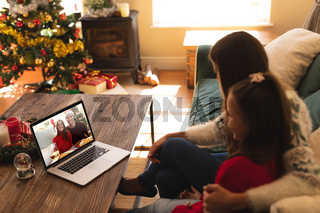 Woman and daughter sitting on couch having a videocall with couple in santa hats smiling on laptop a