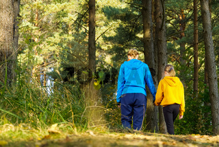Mom with daughter walking in nature on the forest road holding hands. Mother with daughter hiking in autumn pine forest.