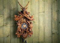 old Black Forest cuckoo clock in front of a green wooden wall