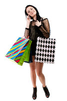 Young woman with shopping bags and mobile phone on a white background