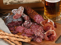 Antipasti dish with bacon, jerky, salami, crispy grissini with cheese. A meat appetizer is a great i