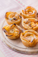 Delicious apple puff pastry in rose shape on wooden board