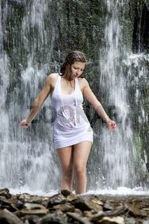 Nasse junge Frau steht im Wasserfall