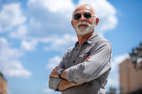Experienced senior man with sunglass and beard on street portrait