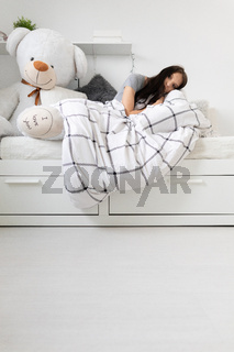 A sick teenager lies under the covers in bed next to her teddy bear.