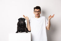 Image of confused man in glasses raising hands and shrugging complicated, standing near black pug dog over white background