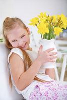 Kind hält Vase mit gelben Osterglocken