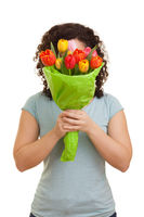 Young natural woman with curly hair hiding behind a bouquet of colorful tulips