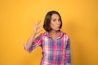 OK or Okay sign with one raised hand smile beautiful woman dressed in a plaid shirt and dark hair on yellow background. Human emotions, facial expression concept