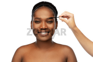face of african woman and hand with mascara brush