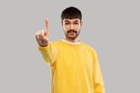 young man in yellow sweatshirt showing one finger