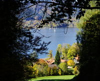 Mountain lake with sailing boat and houses on the shore and forest in beautiful autumn colors