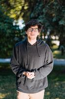 Portrait of happy young male student with glasses in casual outfit