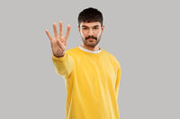 man in yellow sweatshirt showing four fingers