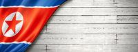 North Korean flag on old white wall banner