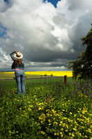Country womanat farm gate watches the clouds over golden crops and fields