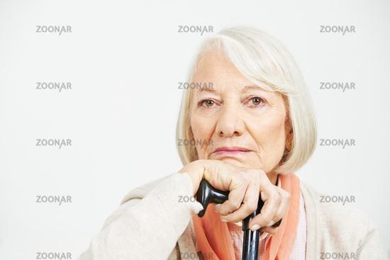 Alte Frau mit Krückstock schaut traurig