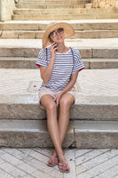 Beautiful young tourist woman at summer vacations, sitting on old stone steps of old medieval Mediterranean costal town, smiling, talking on phone with her loved ones at home