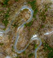 Winding road in the transition from autumn to winter, snow at a germany roa, filmed straight from above.
