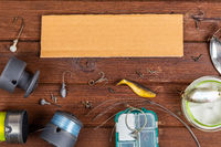 Different fishing tacles with lures and reels on wooden brown background with place for text.