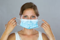 Young woman putting on a surgical mask in studio.