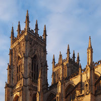 a side view of york minster in sunlight against a blue cloudy sky