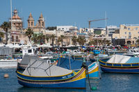 Maltese fishing village of Marsaxlokk with traditional painted boats in Foreground