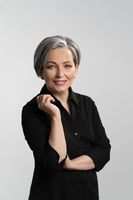 Grey haired mid aged pretty woman looking at camera with arms folded wearing black shirt isolated on grey background. Confident mature grey haired woman. Human emotions, facial expression concept