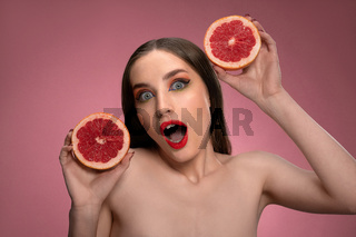 Beauty portrait of an attractive young woman holding two parts of juicy grapefruit sliced in her hands looking surprised. Charming joyful funny lady with long hair isolated on pink background