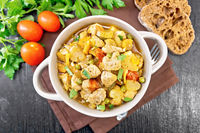 Chicken with vegetables and peas in saucepan on board top