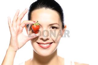Schöne verführerische Frau hält reife Erdbeere