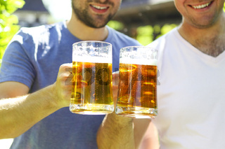 Close up of two young men in casual wear stretching out glasses with beer and smiling