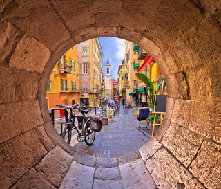 Nice colorful street architecture and church view through stone window