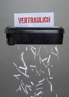 A shredder destroying a document - Confidential - Vertraulich German