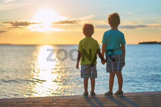 Two cute red curly boys brothers standing on the seashore looking at beautiful sunset sky. Future concept.